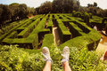 Shoes in front green maze garden feet sneakers with a grass labyrinth background sunny day Stock Image