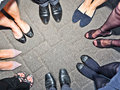 Shoes of party people in a circle standing Royalty Free Stock Images