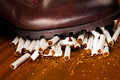 Shoes trampling down on cigarettes give up smoking concept Stock Image