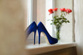 Shoes on window sill blue with rose bouquet Royalty Free Stock Image