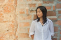 Shoot photo Asian woman portrait wear white shirt and looking sideways with red brick background. Royalty Free Stock Photo