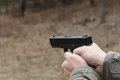 Shooting from a pistol. Reloading the gun. The man is aiming at the target. Shooting range. Man firing usp pistol at target in ind Royalty Free Stock Photo