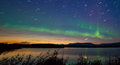 Shooting star meteor aurora borealis northern lights and at midnight in summer over horizon of lake laberge yukon Stock Images