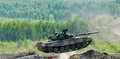 Shooting tank T-80 jumps through ditch Royalty Free Stock Photo