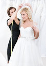 Shop assistant helps to fix the wedding veil Stock Photography