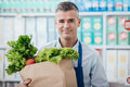 Shop assistant holding a grocery bag Royalty Free Stock Photo