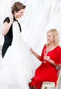 Shop assistant proposes a wedding dress Royalty Free Stock Photo