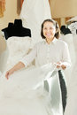 Shop consultant shows bridal dress at wedding store Stock Photography