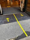 Shop entrance, for social distancing yellow floor sign tape and arrows. Royalty Free Stock Photo