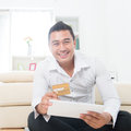 Shop on the internet attractive southeast asian man using a credit card to with a tablet computer asian male model at home Royalty Free Stock Photos