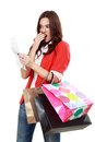 Shopaholic attractive brunette woman looking at her receipt overspending Stock Images