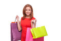 Shopaholic cheerful young woman in red dress holding shopping bags and looking at camera while standing isolated on white Stock Image