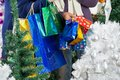 Shopaholic couple carrying shopping bags at midsection of christmas store Stock Image