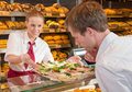 Shopkeeper in bakery showing sandwiches to customer salewoman or presenting tray with Royalty Free Stock Images