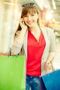 Shopper phoning vertical shot of a happy girl with purchases looking at camera while speaking by the phone Royalty Free Stock Photos