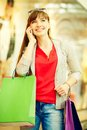 Shopper phoning vertical shot of a happy girl with purchases speaking by the phone Stock Image