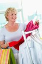 Shopper with tanktop portrait of middle aged woman choosing new in clothing department Royalty Free Stock Photos