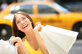 Shopper woman shopping in new york city manhattan usa girl holding bags smiling happy with yellow taxi cab Stock Images
