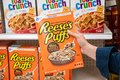 Shoppers hand holding a  package of General MIlls Reese`s Puffs brand sweet and crunchy peanut butter corn puffs cereal Royalty Free Stock Photo