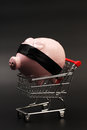 Shopping basket with pink piggy bank with black blindfold inside standing on black background vertical Royalty Free Stock Image