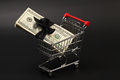 Shopping basket with stack of money american hundred dollar bills with black bow inside standing on black background Royalty Free Stock Photo
