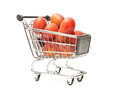 Shopping cart filled with red plums isolated on white Royalty Free Stock Photos