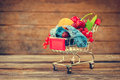 Shopping cart with fruits, berries, tape line on old wood background Royalty Free Stock Photo