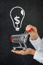 Shopping cart in hands against blackboard with drawing bulb lamp Stock Photos