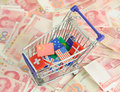 Shopping cart with national flag on a lot of renminbi on white background Royalty Free Stock Photography