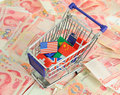 Shopping cart with national flag on a lot of renminbi white background Royalty Free Stock Images