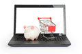 Shopping cart and piggy bank on laptop Royalty Free Stock Photo