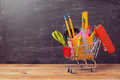 Shopping cart with school supplies over chalkboard background. Back to school sale concept