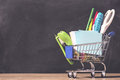 Shopping cart with school supplies over chalkboard background. Back to school sale concept Royalty Free Stock Photo