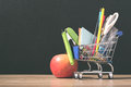 Shopping cart with school supply in front of blackboard. Back to school concept Royalty Free Stock Photo