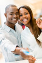 Shopping couple paying with credit card and looking happy Royalty Free Stock Images