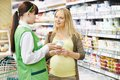 Shopping in dairy supermarket sales assistant demonstrating products food to pregnant female customer during at store Stock Image