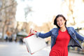 Shopping girl happy shopping outside beautiful woman running joyful with bags outdoors wearing denim jacket on la rambla Royalty Free Stock Images