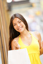 Shopping girl portrait with shopping bags outside shopper woman smiling happy looking at camera in yellow summer dress in outdoors Royalty Free Stock Photography