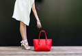 Shopping. girl pulls her hand to the bag. fashion girl in a short white dress in beautiful shoes with ribbons and large Royalty Free Stock Photo