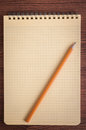 Shopping list blank notepad and pencil laying on it on office wooden table Royalty Free Stock Photos