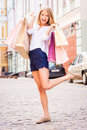 Shopping makes me happy full length of attractive young cheerful woman holding bags and looking at camera while standing outdoors Royalty Free Stock Photography