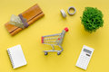 Shopping in online store. Bank card nearby purse, calculator and shopping cart on yellow background top view