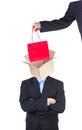 Shopping public values hand putting red bag into man s head represented as an open empty cardbox isolated on white background Stock Photography