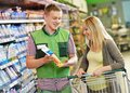 Shopping in supermarket sales assistant demonstrating food to female customer during at store Royalty Free Stock Image