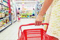 Shopping in supermarket shopper with basket aisle Stock Image