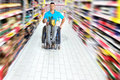 Shopping in supermarket young man wheelchair is Stock Photos