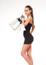 Shopping time portrait of a slender young beauty holding white bags Royalty Free Stock Photo