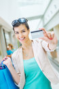 Shopping time young beautiful woman enjoying showing credit card Royalty Free Stock Photos