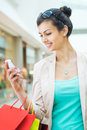 Shopping time young beautiful woman enjoying using cell phone Royalty Free Stock Photos