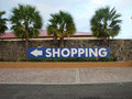 Shopping to the left a big sign with direction arrow in street Stock Photography